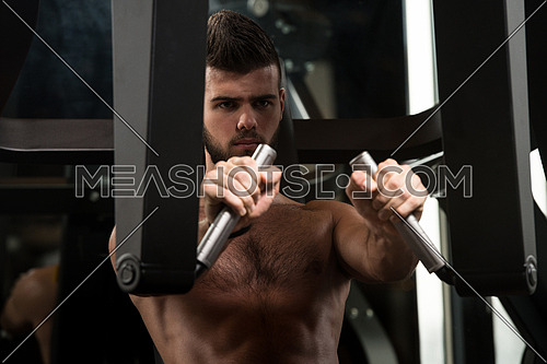 Handsome Man Is Working Out Chest On Machine In A Modern Gym