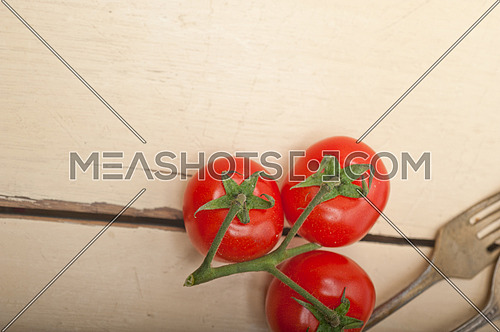 ripe cherry tomatoes cluster over white rustic wood table