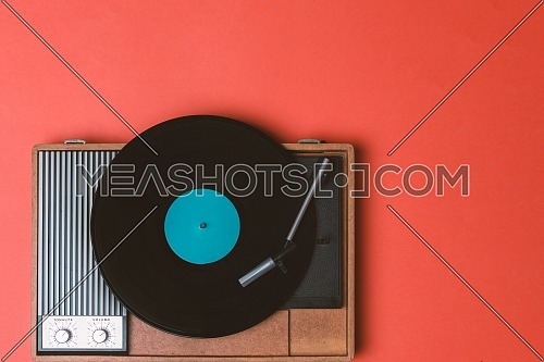Old vinyl player and turnable on a orange background. Entertainment 70s. Listen to music. Top view.