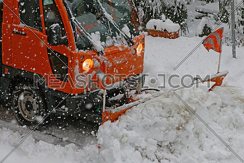 Detail of snow plow truck and blade in action during a heavy snow storm