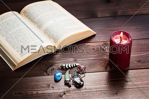 Composition of esoteric objects,candle and book used for healing and fortune-telling.