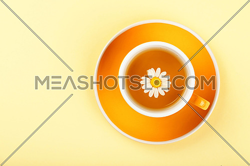 Close up one full yellow cup of herbal tea with camomile flower on saucer over pastel paper background, elevated top view, directly above