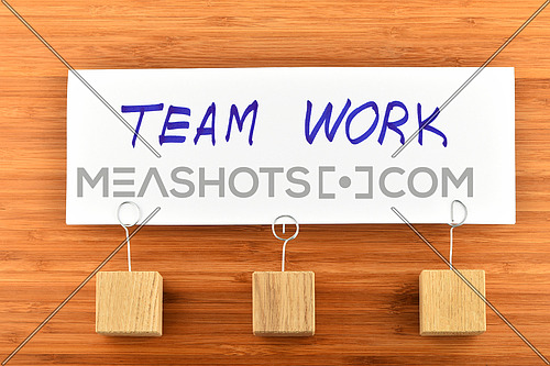 Team work, one big white paper note with three wooden holders on wooden bamboo background for presentation