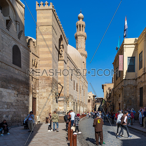 Cairo, Egypt- November 23 2019: Moez Street with local visitors, Minaret of Sultan Barquq Mosque, and Sabil-Kuttab of Katkhuda historic building at the far end, Gamalia district, Old Cairo