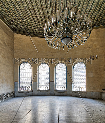 Interior of Sabil (Place providing free drinking water to pedestrians and animals in old Egypt) with iron ornate windows, white marble floor, and huge chandelier. part of the mosque of Soliman Agha El-Selehdar, Cairo, Egypt