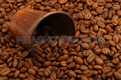 Close up fresh roasted Arabica coffee beans poured out of brown ceramic cup, high angle view