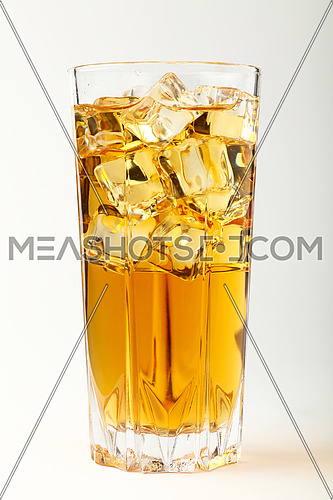 One full high glass of cold iced black tea with transparent ice rocks cubes over white, close up, low angle view