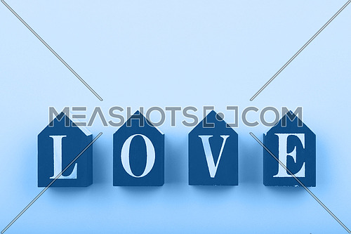 Close up wooden house shaped cube signs with LOVE word over pastel blue background and copy space, low angle view