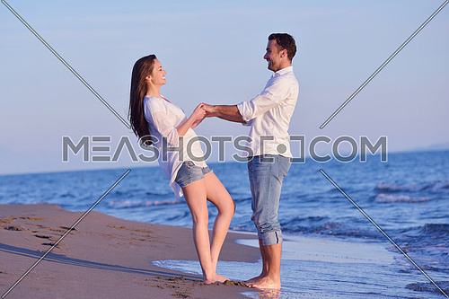 happy young romantic couple in love have fun on beautiful beach at beautiful summer day