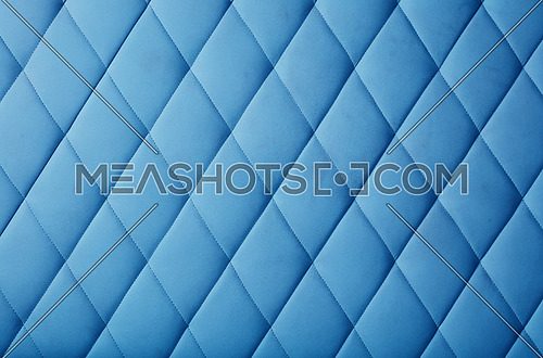 Background texture of pastel blue genuine leather soft tufted furniture or wall panel upholstery with deep diamond pattern, close up