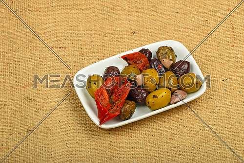 White plate of Mediterranean snack of red and green olives and pickled red pepper on burlap jute canvas