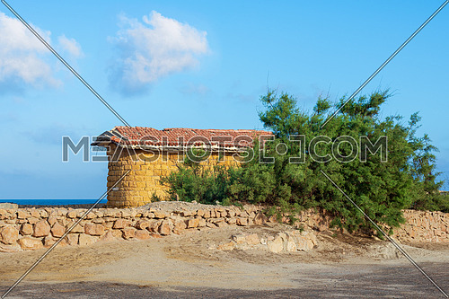 Abandoned building built of stone bricks and red tiled roof, short green tree and stone fence on background of partly cloudy sky and calm sea, Montaza Park, Alexandria, Egypt