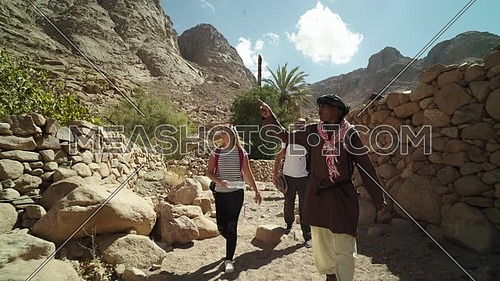 Follow shot for group of tourists walking on big rocks between two fences of rocks with bedouin guide showing almond trees while explore Sinai Mountain for wadi Freij at day.