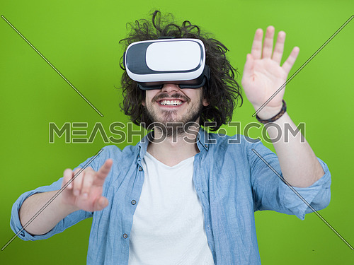 Happy man getting experience using VR headset glasses of virtual reality, isolated on green background