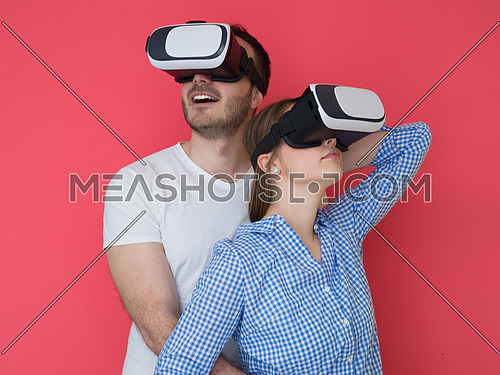 happy young couple getting experience using VR-headset glasses of virtual reality isolated over red background