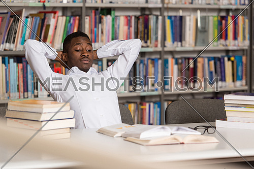 Stressed African Student Of High School Sitting At The Library Desk - Shallow Depth Of Field
