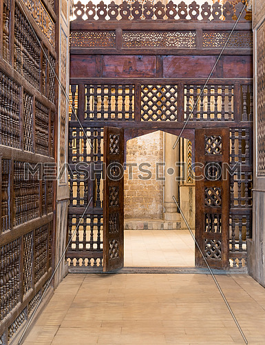 Interleaved wooden wall (mashrabiya) with wooden ornate door in Sultan Qalawun mosque, a historic mosque in Old Cairo, Egypt