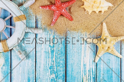 Decorative steering wheel with starfish, seashells on the sandy beach old blue wood background
