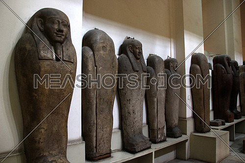 a photo from inside the Egyptian museum showing display of ancient statues and mummies cover used during the pharaohs civilization