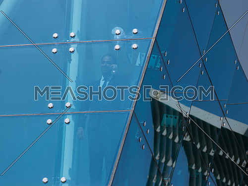 senior business man talking  on mobile phone  at modern office building outdoor shoot with blue sky in background