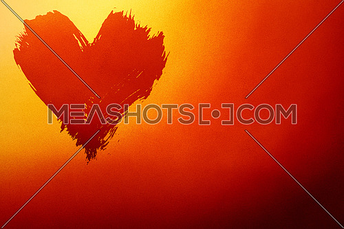 Abstract colorful background with brushstroke painted grunge heart over red and yellow gradient noise grain texture with copy space