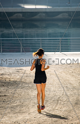 a woman jogging beside the water