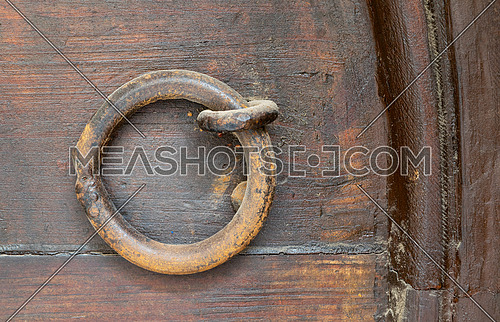 Closeup of rusted ring door knocker over an aged wooden door