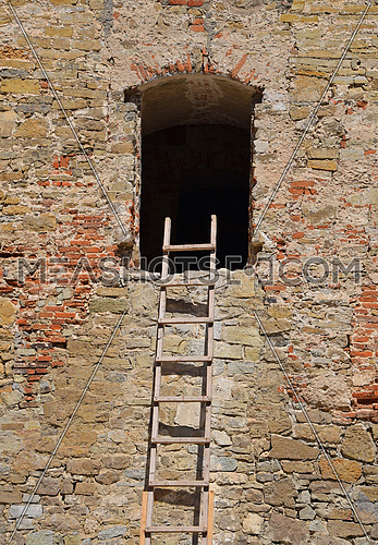 Wooden ladder next to empty window of old vintage stone wall of medieval building