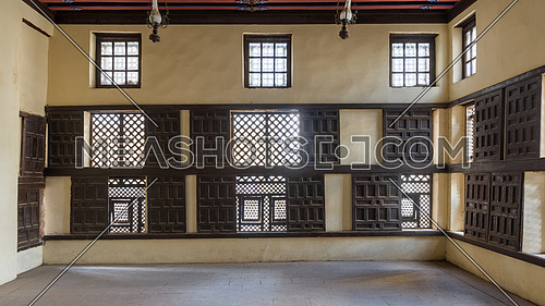 Interior wall with decorated lattice wooden windows, Mashrabiya, and sliding wooden shutters at ottoman era Amasely historic house, Rosetta City, Egypt