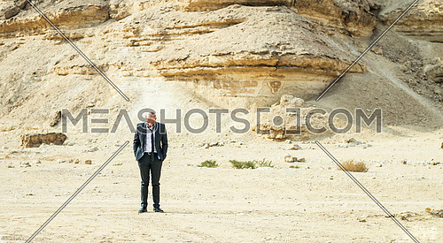A Man smiling & looking down alone in empty desert