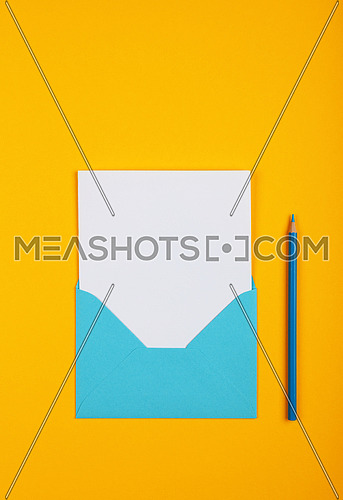 One open blank pastel blue envelope with white paper and wooden pencil over vivid yellow background, flat lay, directly above