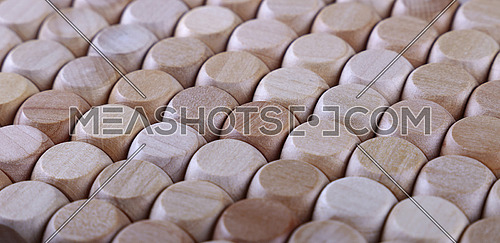 Close up background pattern of natural wooden dice shaped toy building blocks, high angle view perspective
