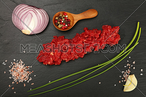 Raw minced beef red meat cutlet, spices, peppercorn in wooden scoop, spring green chive, onion, garlic cloves and Himalayan salt on black slate board, close up, elevated top view, directly above