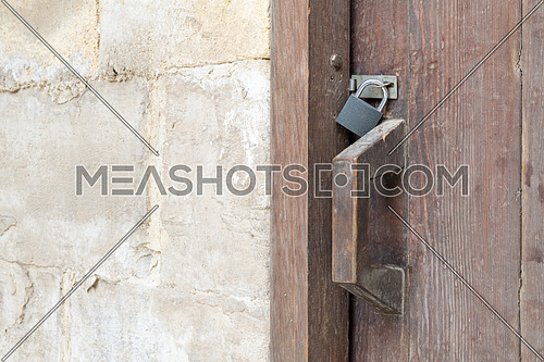 Closeup of a wooden aged latch locked with a padlock over a wooden door and stone wall