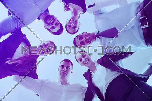 Closeup of happy business people with their heads together representing concept of ftiendship and teamwork isolated on white background