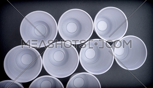 Several white plastic glasses seen from above isolated in black background