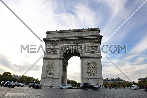 Beautiful night view with car traffic and rush at eavning of the Arc de Triomphe, Paris, France.