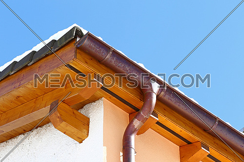 New roof top detail with ceramic tiles and copper water gutter with snow against blue skies