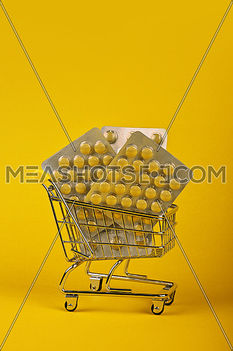 Close up several different blister packs of pills in small shopping cart over yellow background, concept of online medicine order delivery, low angle view