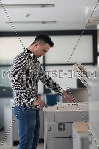 young business man copy documents on copy machine at modern startup office interior, casual clothes