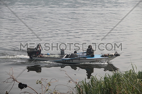 a photo for fishermen in their boat fishing in River Nile in Cairo ,Egypt , the editorial value might come from tackling Fishing activities