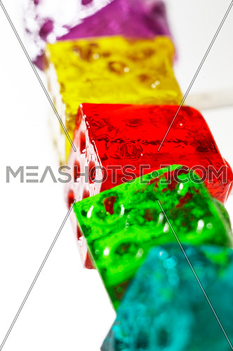 bounch of colorfull translucent dice shaped lollipops backlit on white background