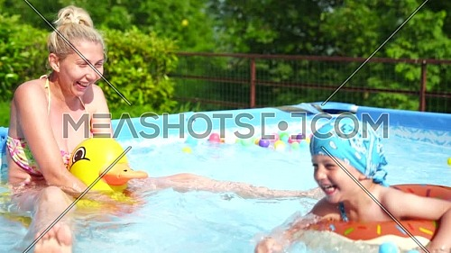Mom and baby play happily in the small pool.Sunny day, family and summer concept