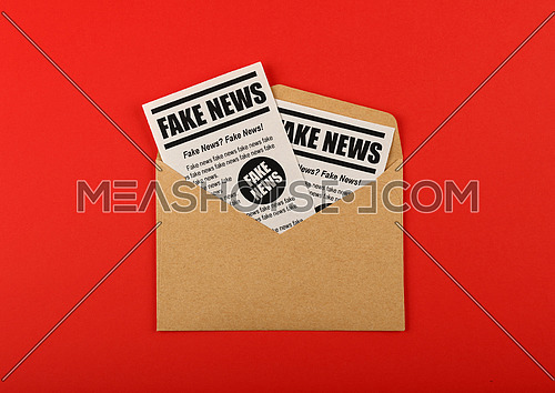 Close up brown paper mail envelope with FAKE NEWS newspapers over red background with copy space, elevated top view, directly above
