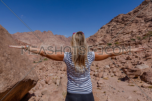 Long shot for a female tourist from behind exploring Sinai Mountain for wadi Freij by day.