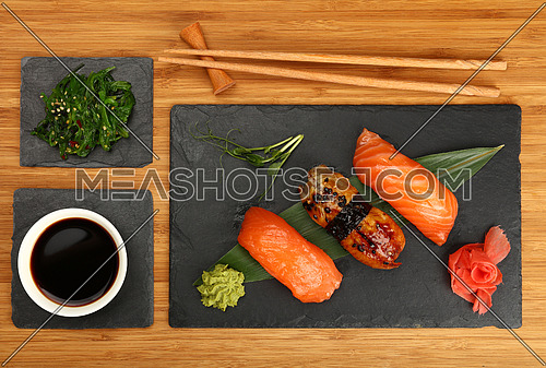Close up set of three nigiri sushi with salmon and eel fish served on black slate board over wooden table, elevated top view, directly above