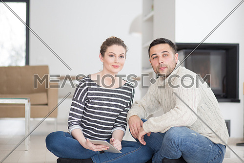 Young Couple on the floor in front of fireplace surfing internet using digital tablet on cold winter day