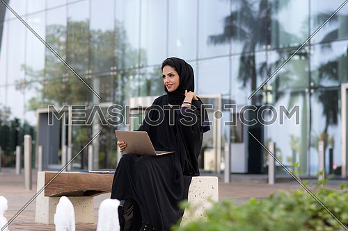Businesswoman working in laptop outdoor