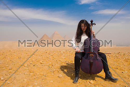 young famale chello player in egyptian desert with pyramids in background