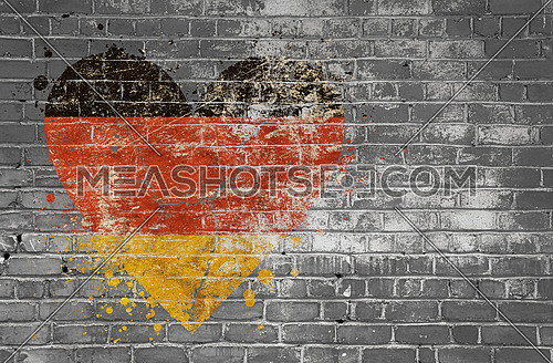 Grunge distressed heqart shaped flag of Germany painted on old weathered grey brick wall
